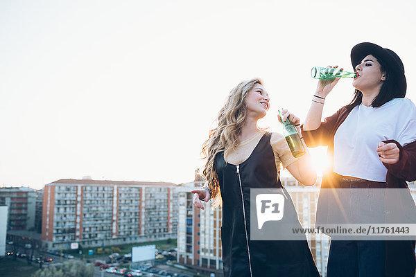 Zwei junge Frauen  auf dem Dach  trinken Flaschenbier