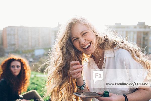 Junge Frau hält Smartphone in der Hand und lacht