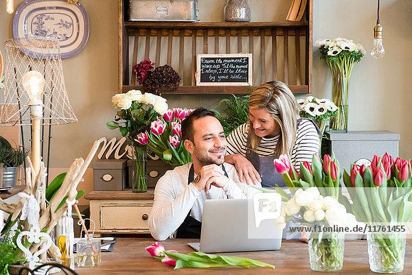 Zwei Floristen im Blumengeschäft  Mann mit Laptop  Frau neben ihm stehend