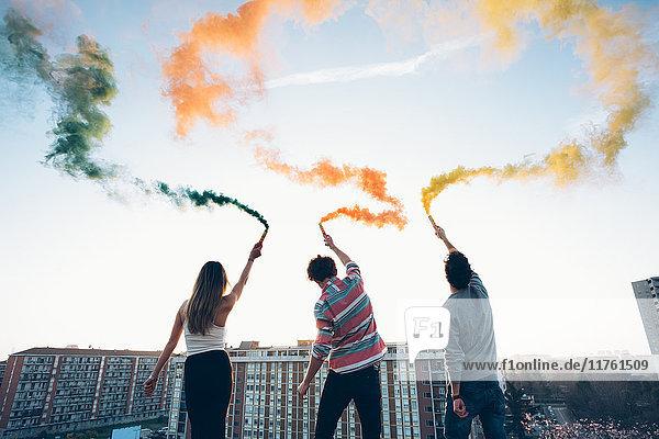Gruppe von Freunden auf dem Dach  mit bunten Rauchfackeln in der Hand  Rückansicht