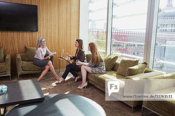 Treffen von Geschäftsfrauen auf einem Bürosofa  London  UK Treffen von Geschäftsfrauen auf einem Bürosofa, London, UK
