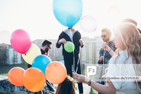 Gruppe von Freunden genießt Dachparty  junge Frau hält Heliumballons