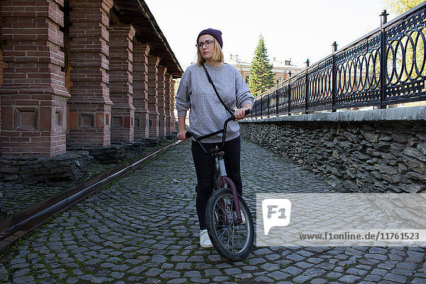 Young woman with BMX bicycle in cobbled street