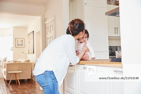 Frau küsst Baby-Tochter auf Küchentresen auf die Stirn