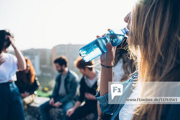 Gruppe von Freunden genießt Dachparty  junge Frau trinkt aus Wasserflasche