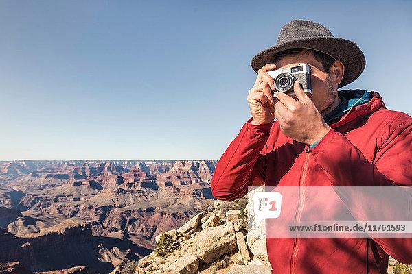 Male tourist photographing Grand Canyon National Park  Arizona  USA