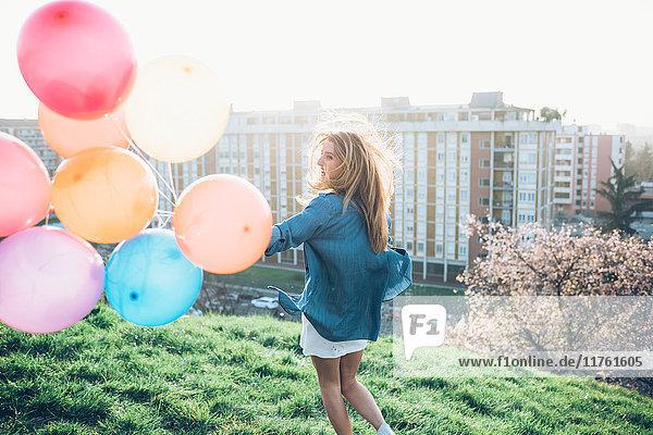 Junge Frau steht auf dem Dach und hält Heliumballons