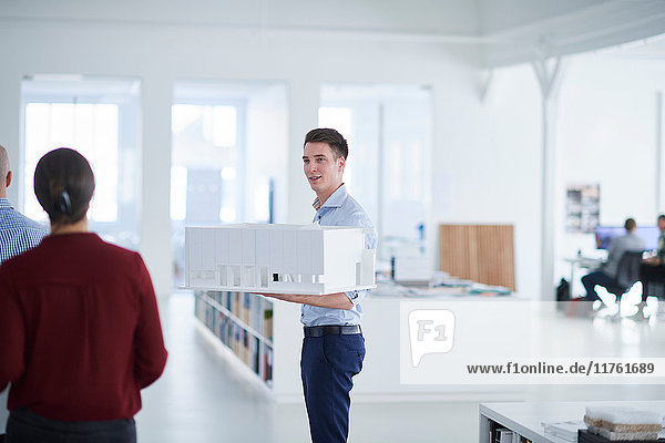 Man in open plan office holding architectural model