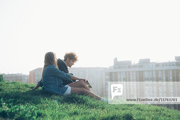 Junges Paar sitzt auf einem Grasrand mit Blick auf die Dächer
