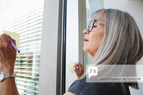 Geschäftsfrau schreibt Ideen auf Glasfenster Geschäftsfrau schreibt Ideen auf Glasfenster