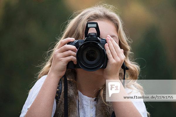 Porträt eines Mädchens  das mit einer digitalen Spiegelreflexkamera fotografiert