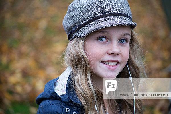 Portrait of blond girl in baker boy cap listening to earphone music