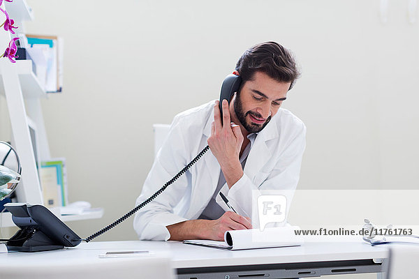 Doctor at desk making telephone call