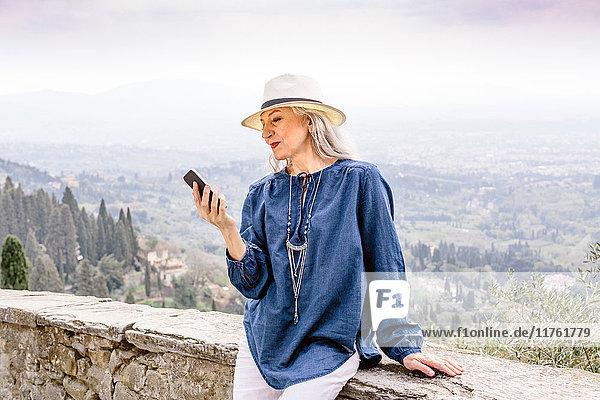 Stilvolle  reife Frau schaut auf Smartphone  Fiesole  Toskana  Italien
