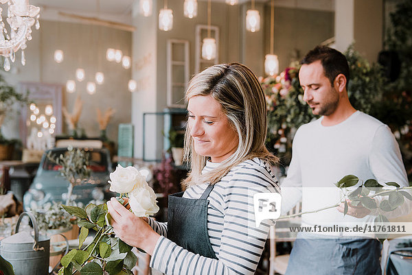 Two florists in flower shop  arranging flowers