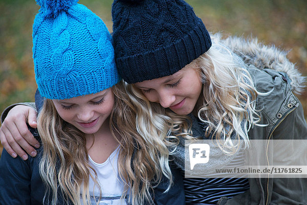 Blond haired sisters wearing knit hats looking down in garden