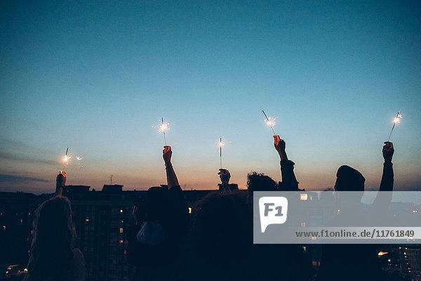 Gruppe von Freunden genießt Dachparty  hält brennende Wunderkerzen in der Luft  Rückansicht
