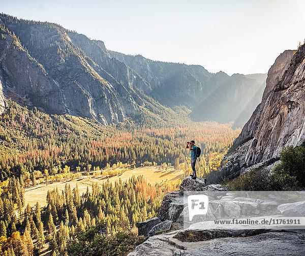 Man on rocky edge looking out through binoculars  Yosemite National Park  California  USA