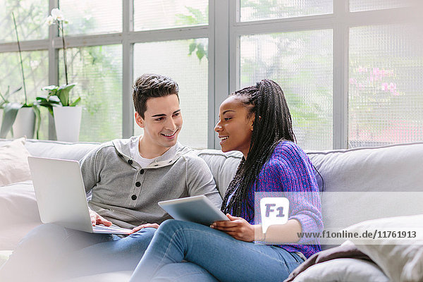 Couple with laptop sitting on sofa talking