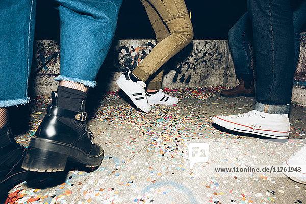 Gruppe von Freunden  im Freien stehend  Konfetti auf dem Boden  niedriger Schnitt