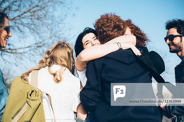 Gruppe von Freunden umarmend  im Freien