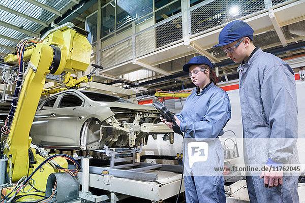 Auszubildende Ingenieure mit Autodichtungsroboter in Autofabrik