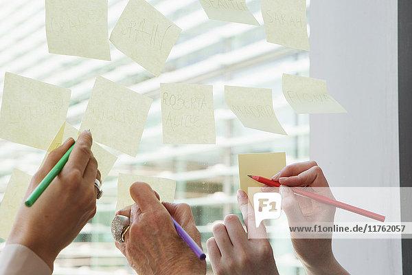 Geschäftsfrauen beim Brainstorming von Ideen zum Glasfenster Geschäftsfrauen beim Brainstorming von Ideen zum Glasfenster