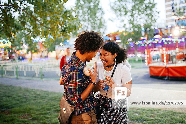 Two friends at funfair  laughing  boy holding ball