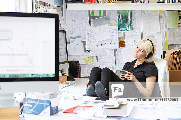 Designerin mit erhobenen Füßen am Schreibtisch  die Kopfhörermusik hört