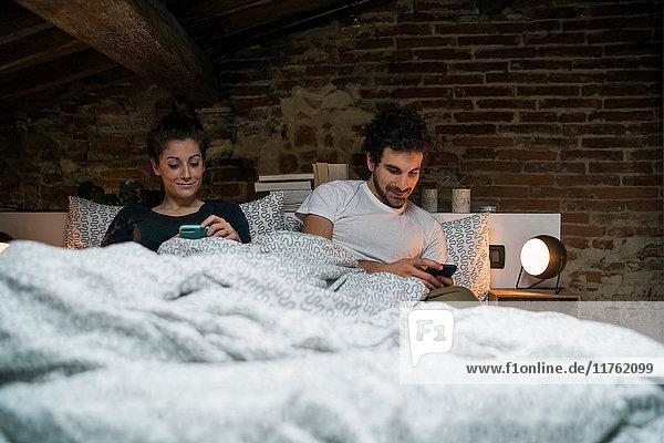 Paar sitzt im Bett und schaut auf Smartphones