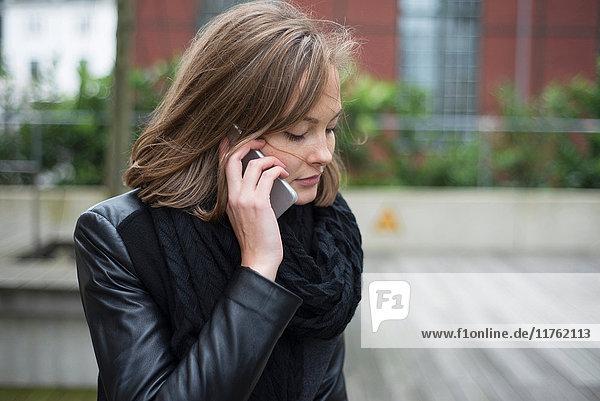 Junge Geschäftsfrau telefoniert mit Smartphone in der Stadt