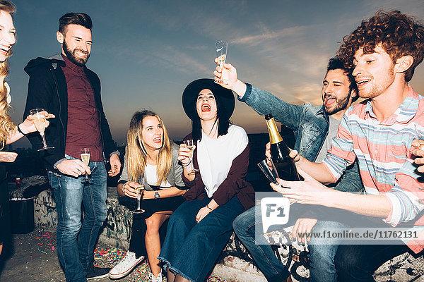 Gruppe von Freunden genießt Dachfeier  hält Sektgläser in der Hand  bringt einen Toast aus
