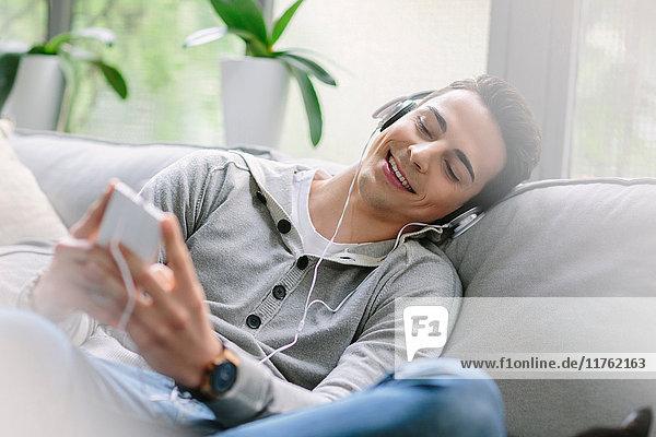 Mann mit Kopfhörern auf dem Sofa sitzend