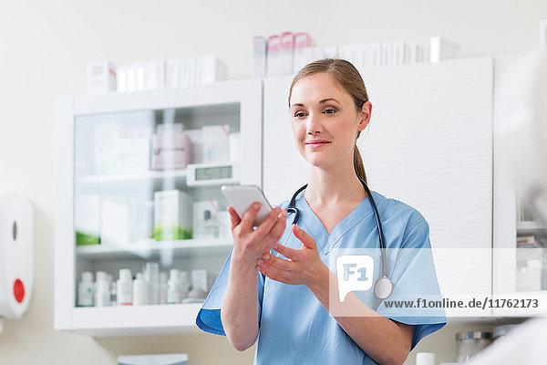 Arzt im Krankenhaus hält Mobiltelefon in der Hand und schaut lächelnd in die Kamera
