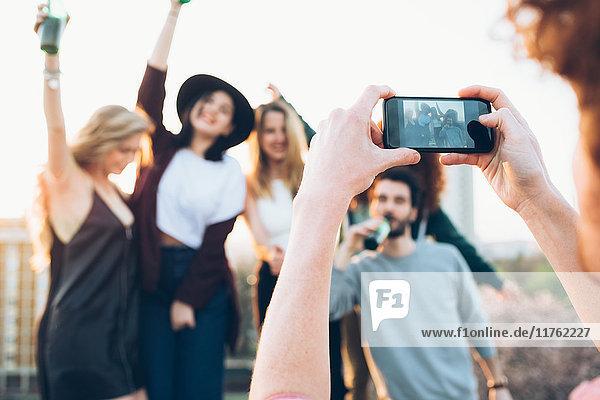 Gruppe von Freunden genießt Dachparty  junger Mann fotografiert mit Smartphone