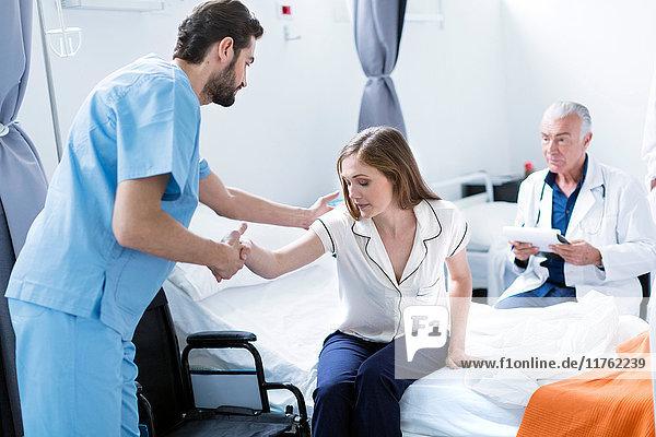 Arzt hilft Patient aus dem Krankenhausbett
