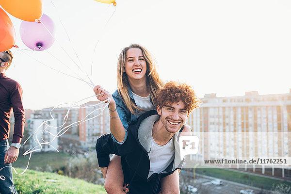Freunde genießen Dachfeier  Junger Mann gibt junger Frau Huckepack