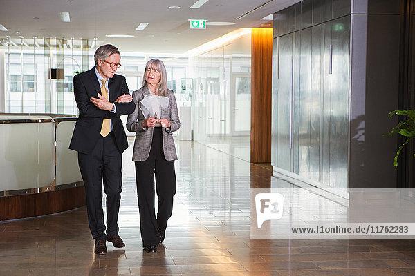 Geschäftsmann und Geschäftsfrau diskutieren im Gehen Geschäftsmann und Geschäftsfrau diskutieren im Gehen