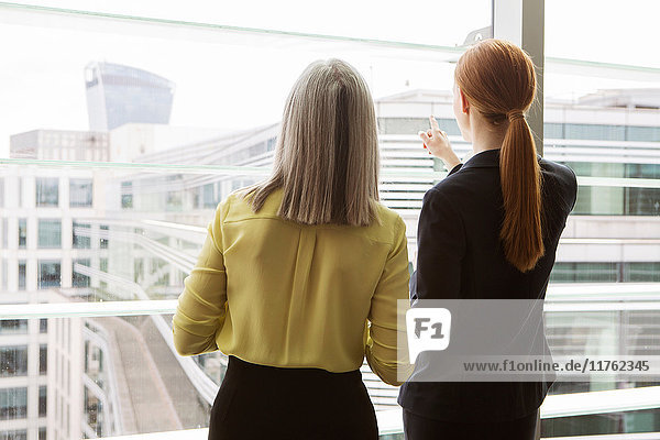 Geschäftsfrauen stehen am Fenster im Büro  London  UK Geschäftsfrauen stehen am Fenster im Büro, London, UK