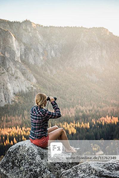 Frau sitzt auf einem Felsblock und schaut durch ein Fernglas hinaus  Yosemite National Park  Kalifornien  USA