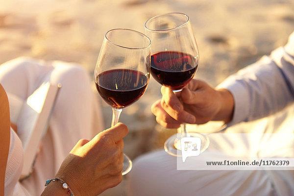 Ehepaar trinkt Rotwein am Strand