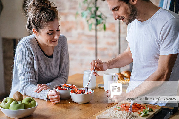 Young couple eating fruit breakfast at kitchen counter