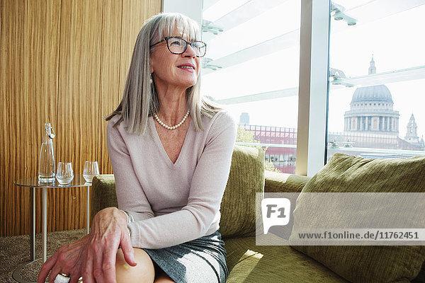 Geschäftsfrau  die im Büro auf einem Sofa sitzt  London  UK Geschäftsfrau, die im Büro auf einem Sofa sitzt, London, UK