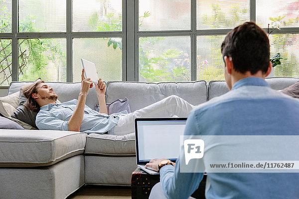 Männer entspannen auf dem Sofa mit digitalem Tablet und Laptop