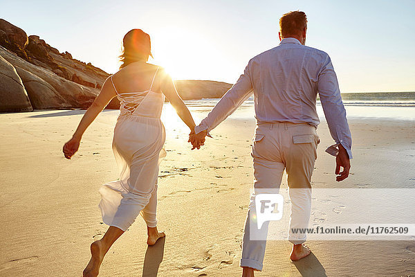 Mature couple walking along beach  hand in hand  rear view  Cape Town  South Africa