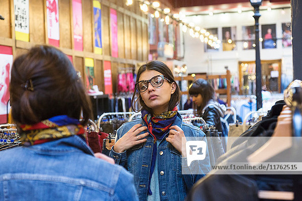 Over shoulder mirror image of young female shopper trying on scarf in market hall
