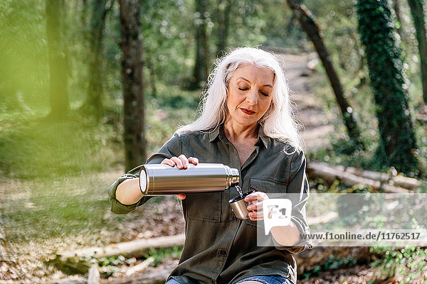 Ältere Backpackerin gießt im Wald Getränkeflaschen aus  Scandicci  Toskana  Italien