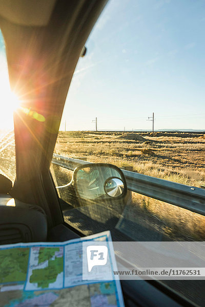 Wing mirror view of man with map on the road in sunlight  Arizona  USA