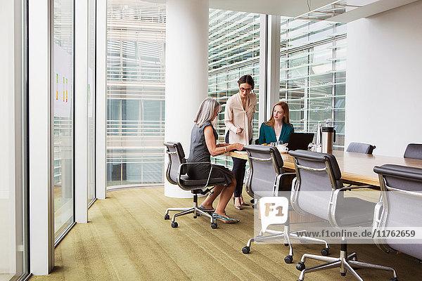 Geschäftsfrauen bereiten Präsentation im Sitzungssaal vor Geschäftsfrauen bereiten Präsentation im Sitzungssaal vor