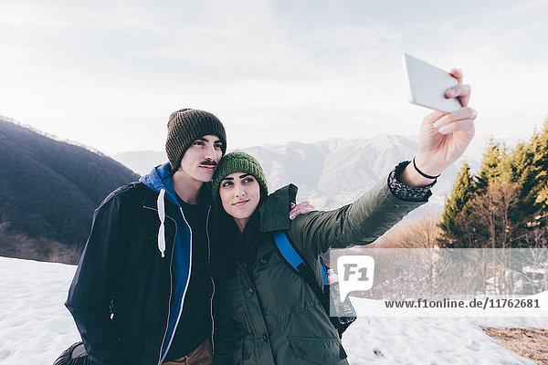 Wanderndes Ehepaar beim Selbstvergnügen in verschneiten Bergen  Monte San Primo  Italien